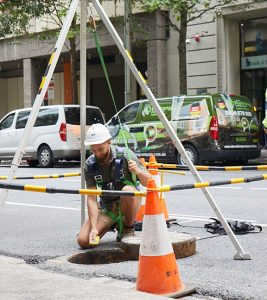 A Relining Company employee navigating a city sewer