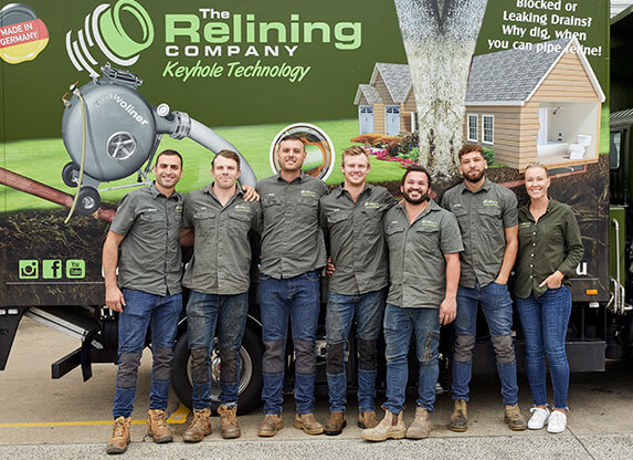 A group of 7 Relining Company employees in front of a truck