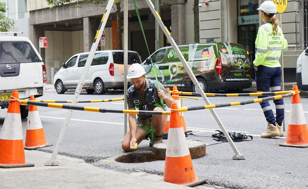 Pipe Relining Employee working on a city street sewer