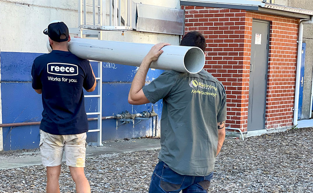 Two pipe relining employees carrying a big pipe on their shoulders
