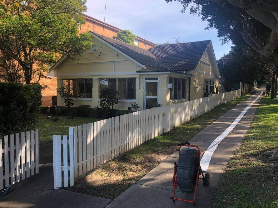 A house with a picket fence and a pipe relining machine on the sidewalk