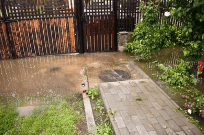 A small fenced in yard overflowing with sewer water
